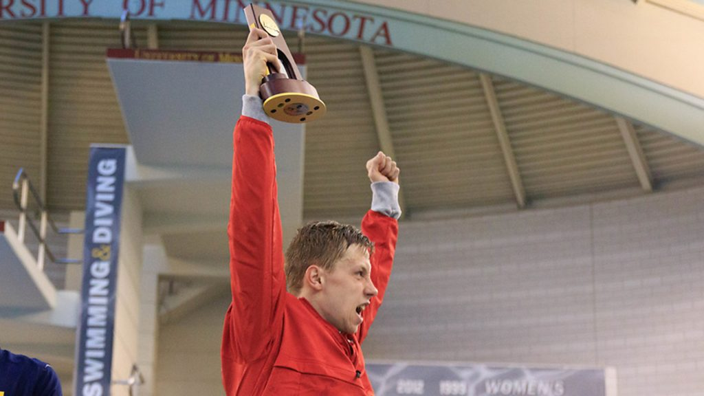 Ipsen holding a trophy over his head.