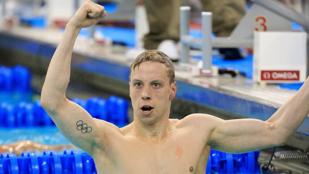 Anton Ipsen in the pool with his fist raised in a victory salute.