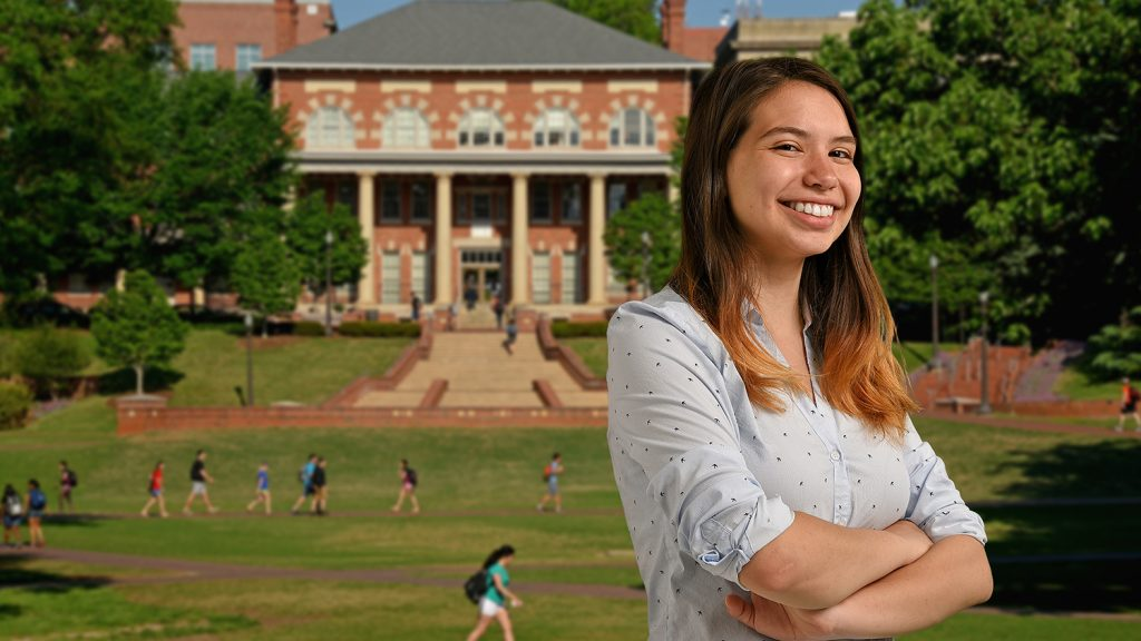 Ana Sofia Uzsoy stands in front of the Court of North Carolina on NC State's campus.