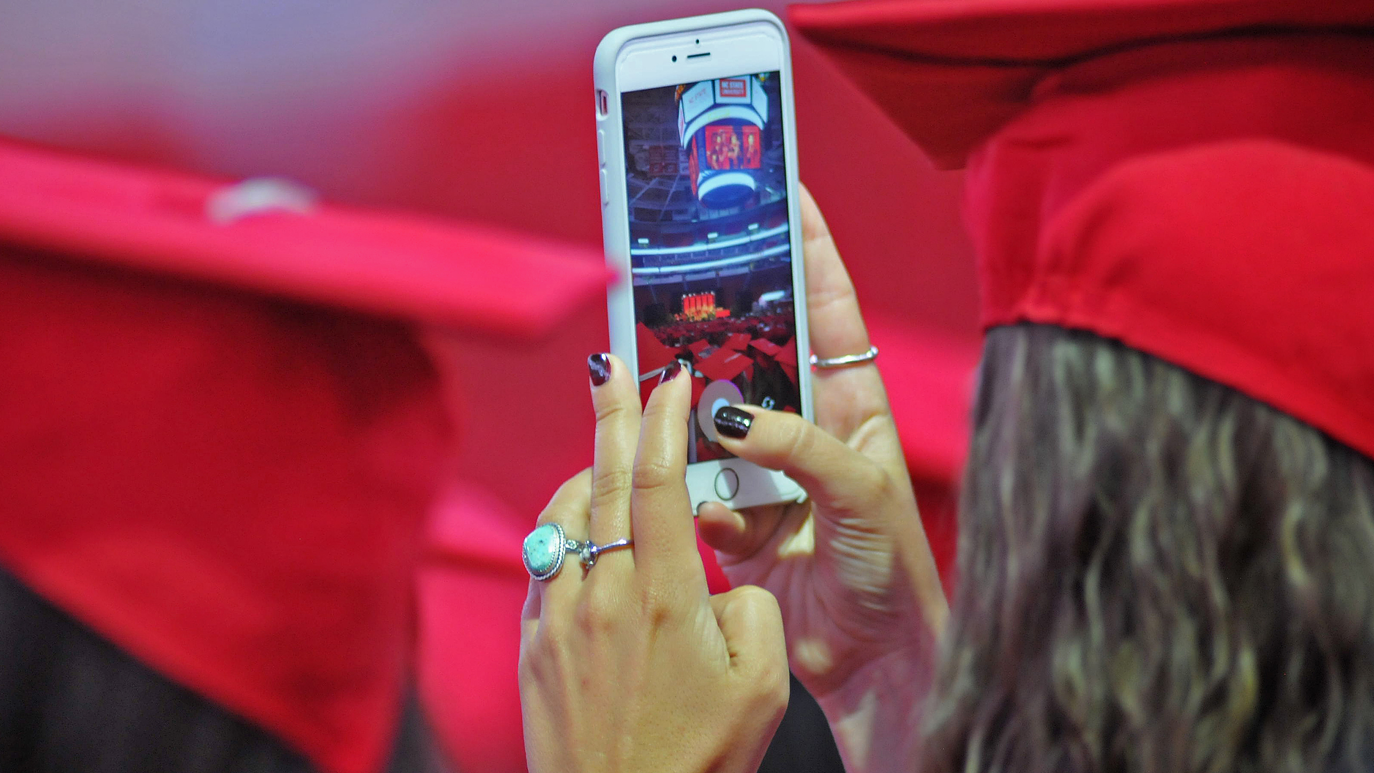 A graduating student takes a cell phone picture during commencement.