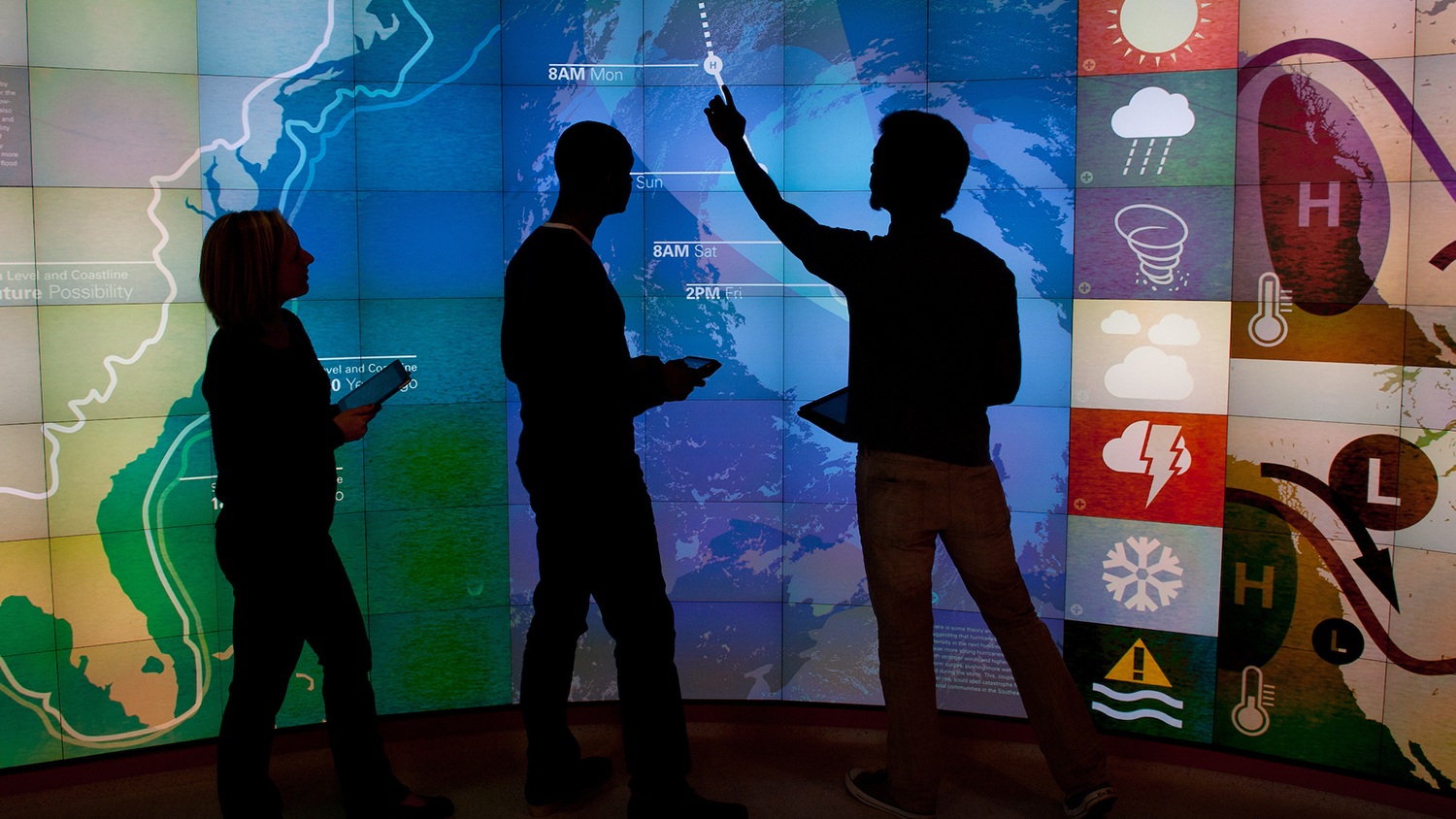 Students point at map in visualization lab.