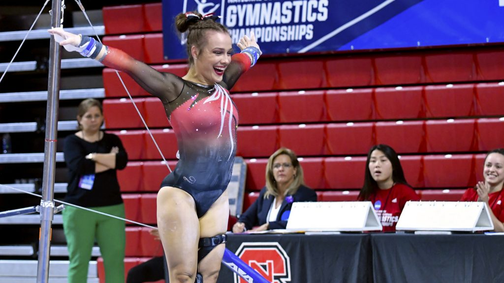 Gymnast Maggie Tamburro raises her arms after completing a dismount at a gymnastics competition