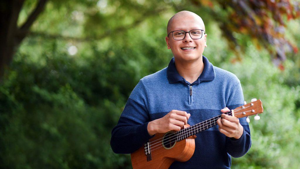 NC State student outside holding a ukulele