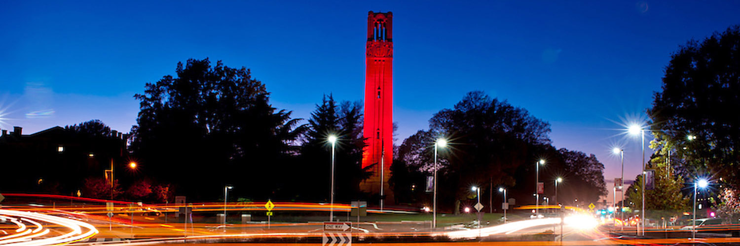 belltower lit up red with moving traffic