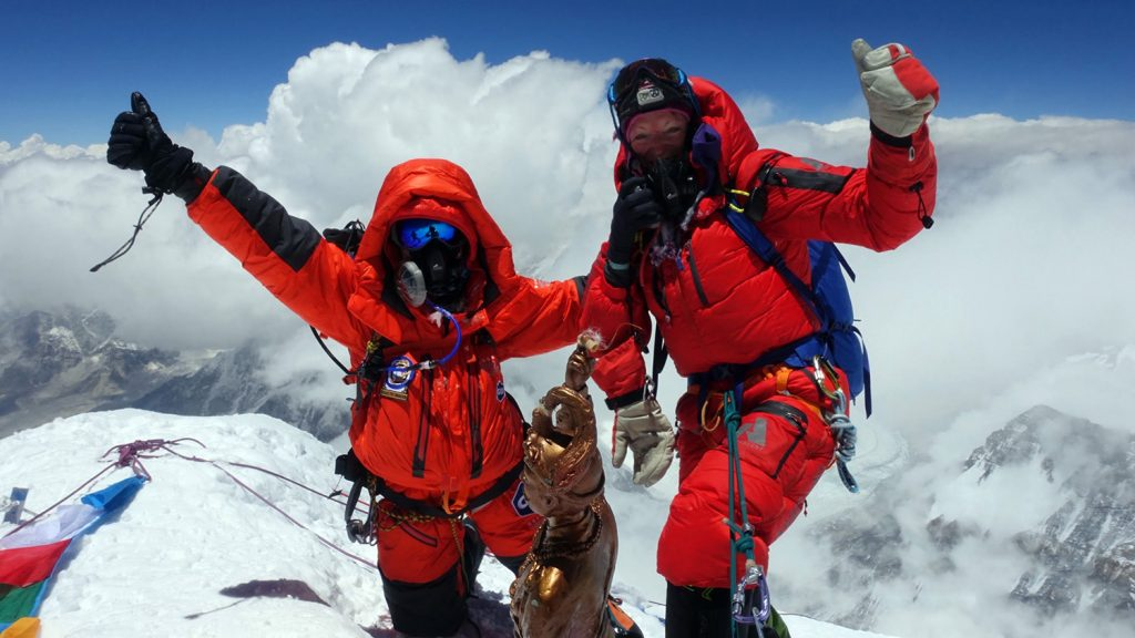 Two climbers at the top of Everest, giving a thumbs-up signal.