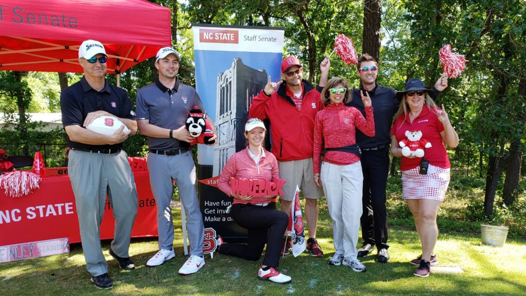 NC State staff pose in front of a red tent at a golf tournament