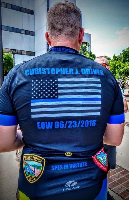Kendrick stands with his back to the camera. His shirt is emblazoned with an American flag and the name of fallen officer Chris Driver.