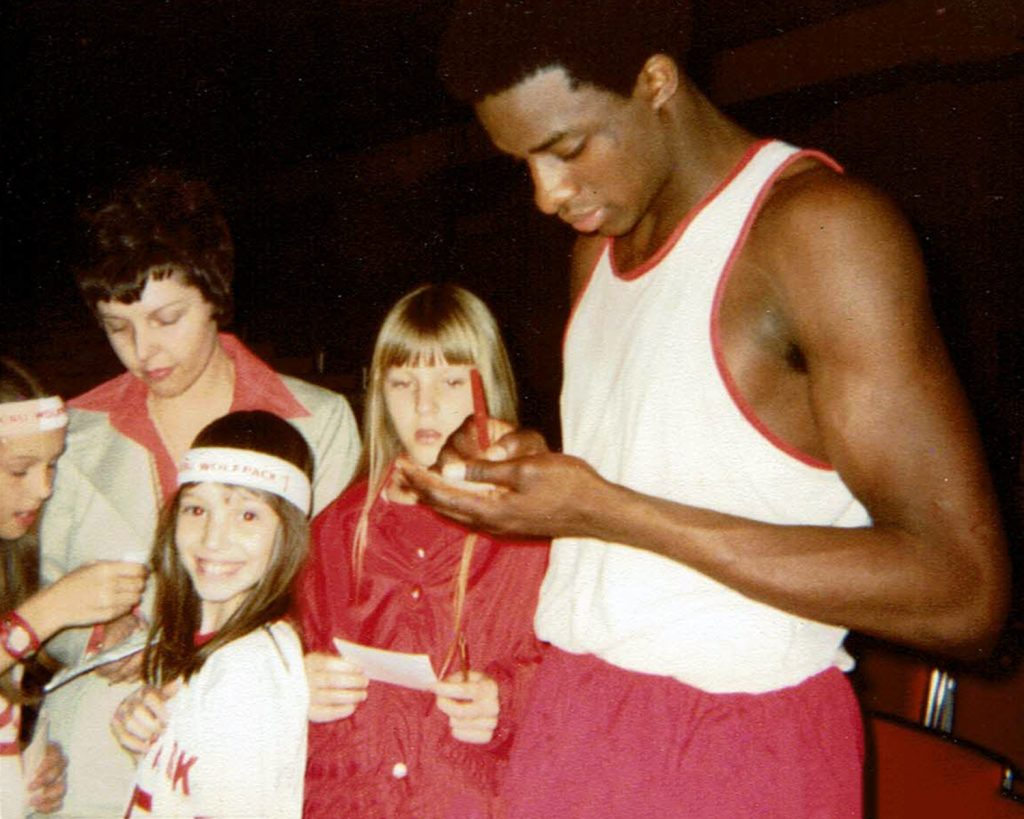Basketball player signs autographs for kids.