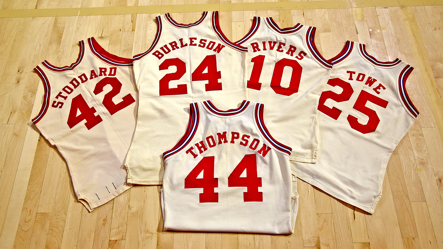 Five jerseys laid out on the floor of Reynolds Coliseum.