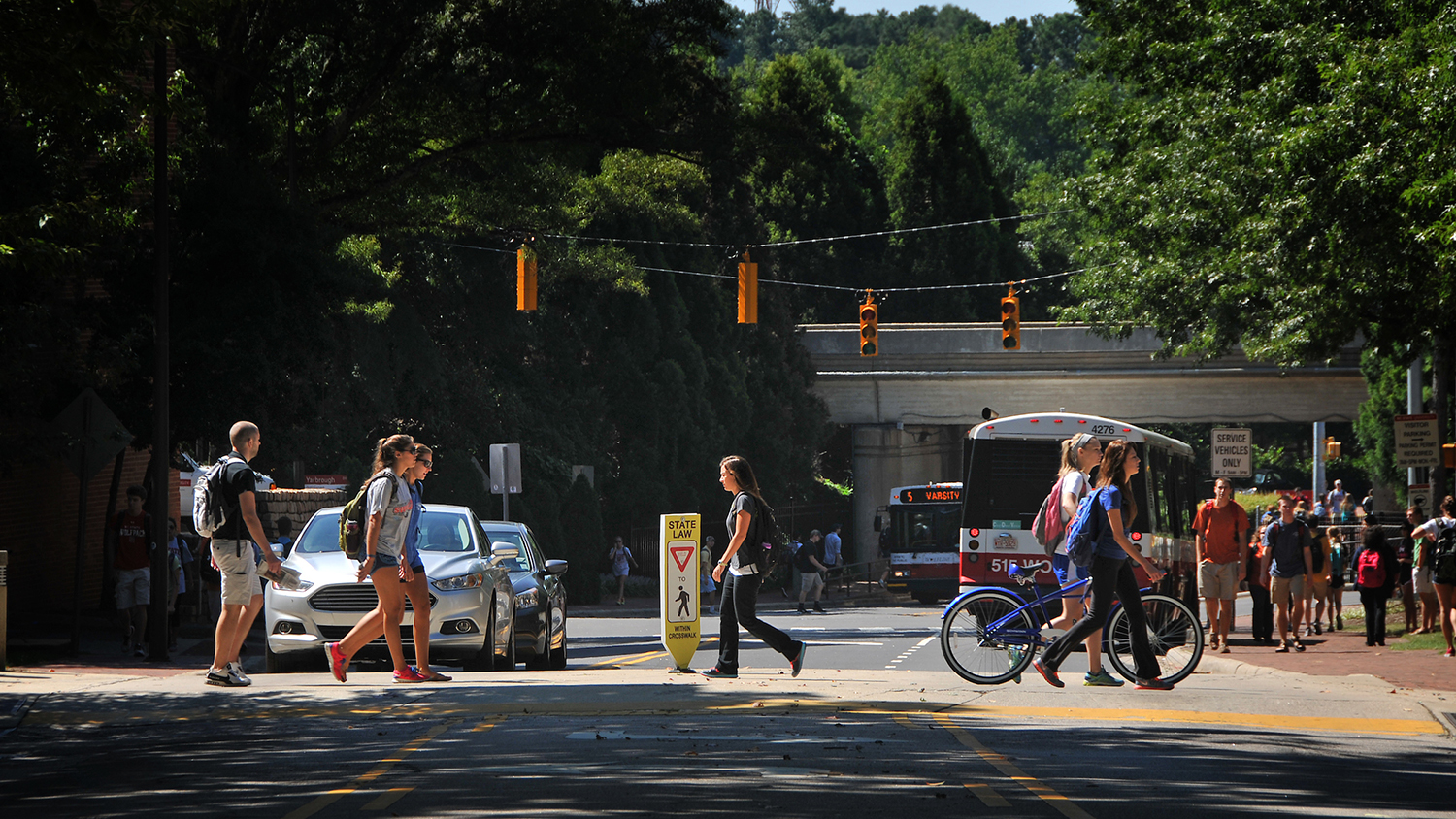 Students cross over Dan Allen Drive as traffic waits.