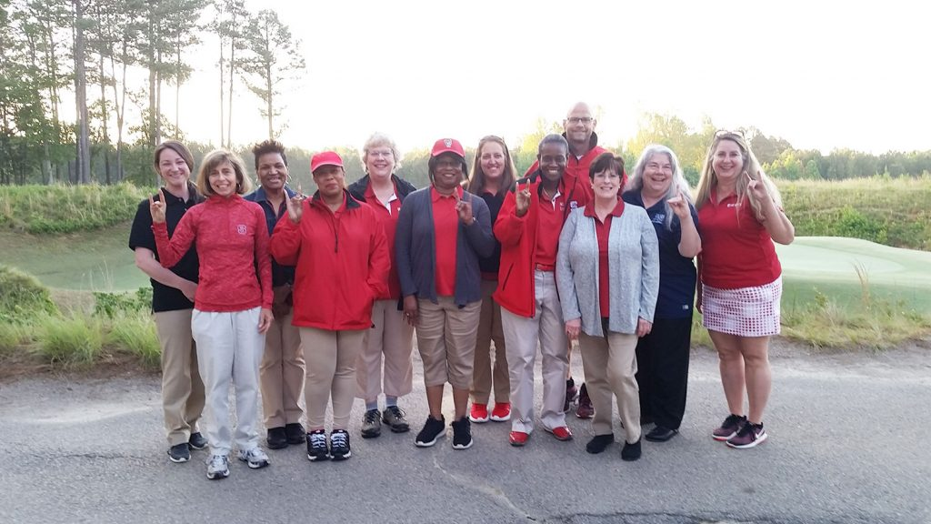 A group of NC State Staff Senate volunteers posing for a photo on a golf course
