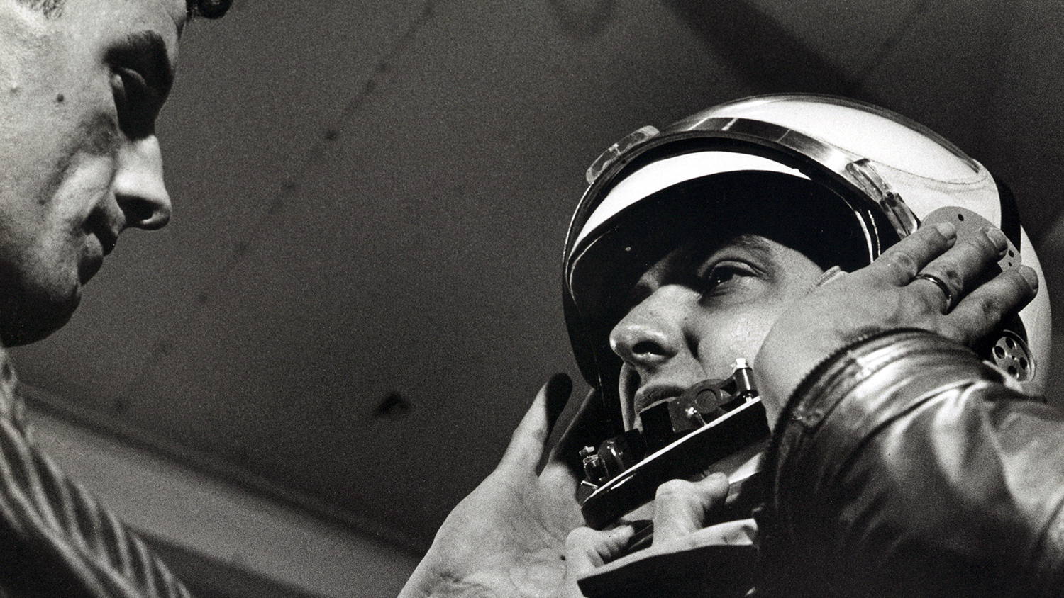A black and white photo of a man fitting a space helmet.