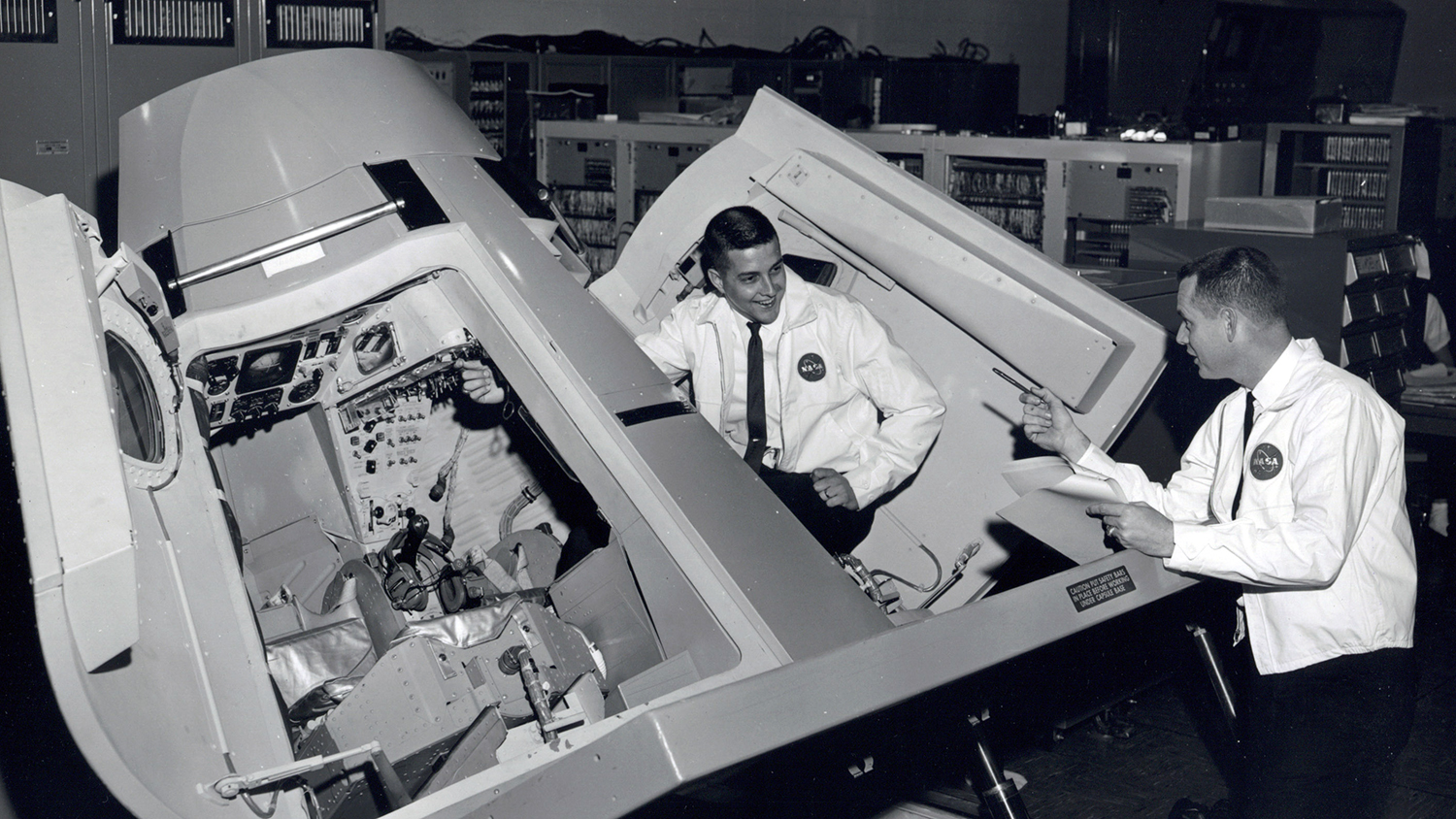 Jim Prim and George Prude pose in the Gemini Trainer used in the Apollo 11 mission.