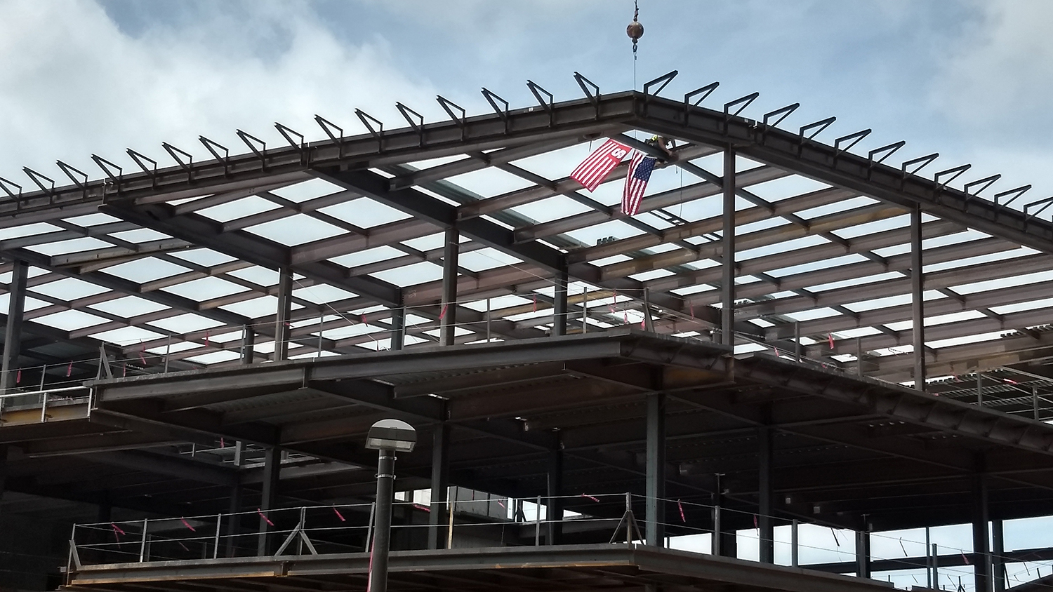 Workers attach a steel beam to the structure of the new Wellness and Recreation Center.