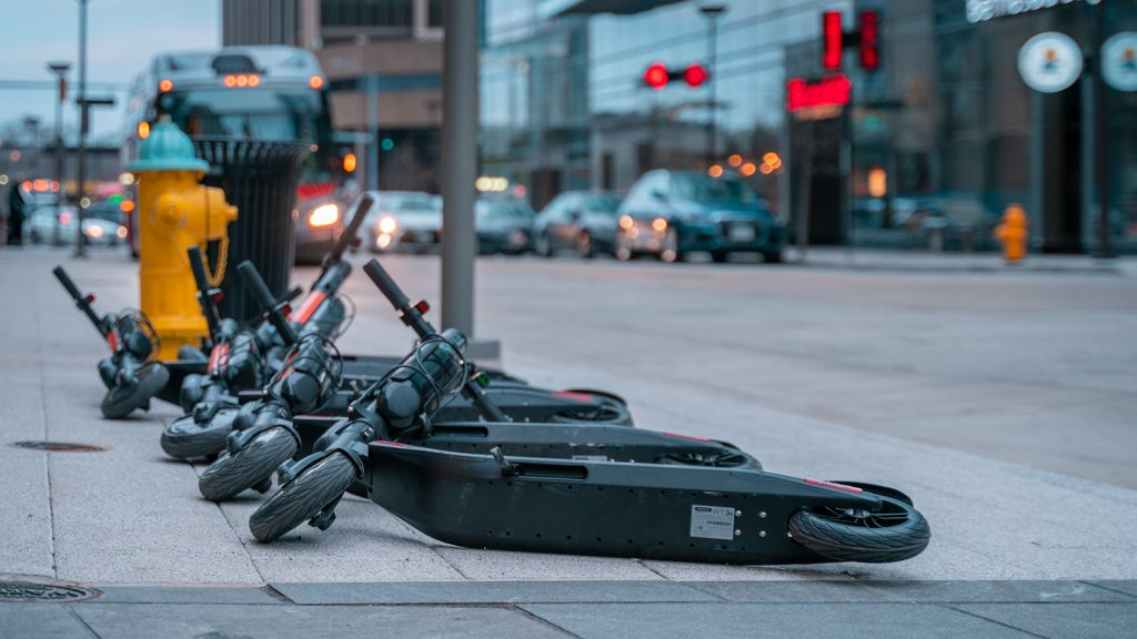 several e-scooters knocked over on a sidewalk