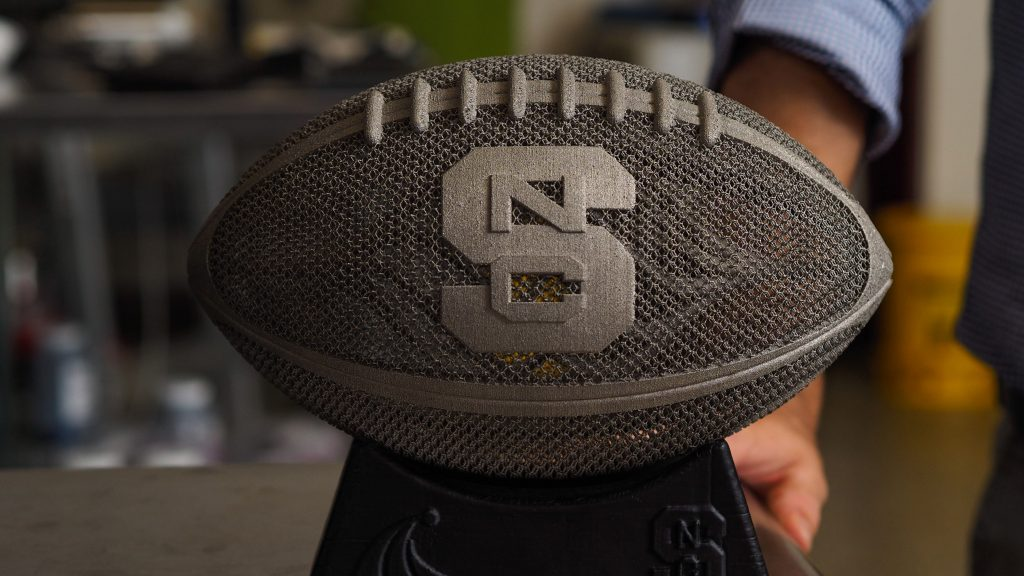 A 3D-printed, lifesize titanium football with a block S.