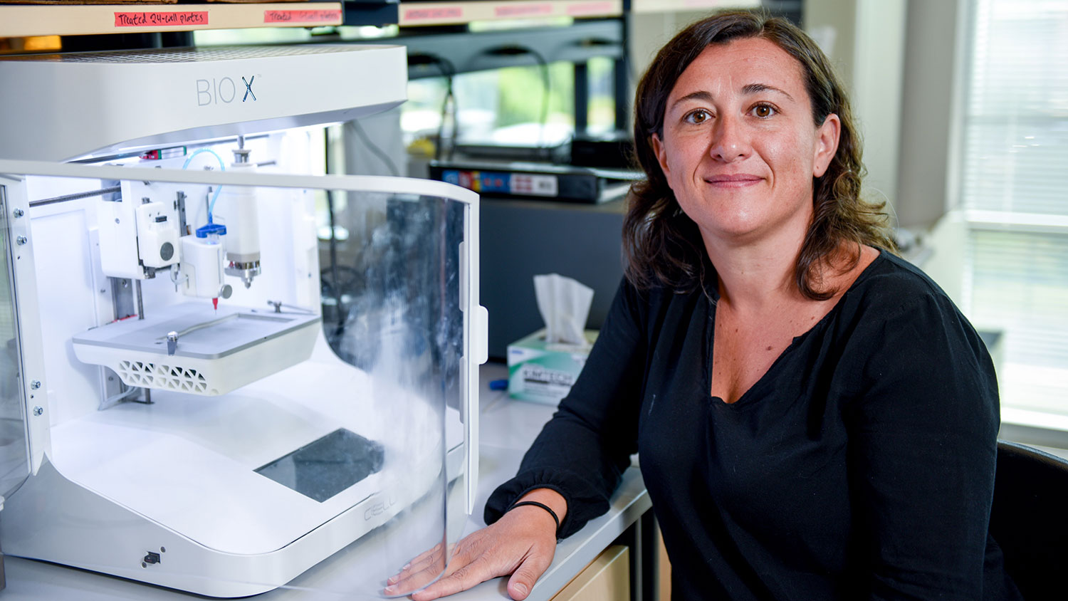 Ross Sozzani next to a 3D bioprinter she uses for her research