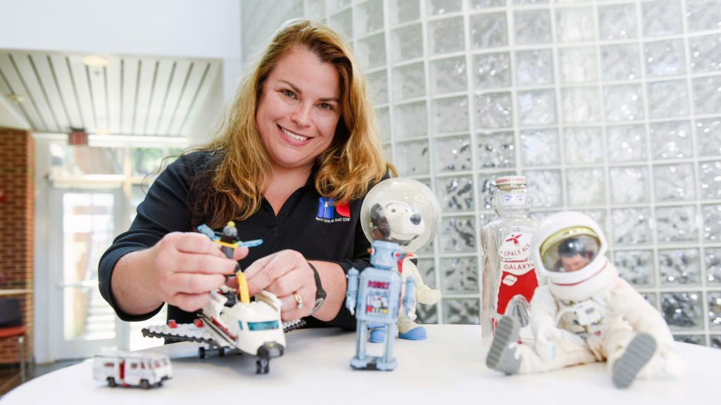 Jobi Cook, assistant director of North Carolina Space Grant, with space-related toys on a table.
