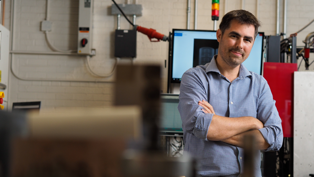 Tim Horn stands in the Center for Additive Manufacturing and Logistics