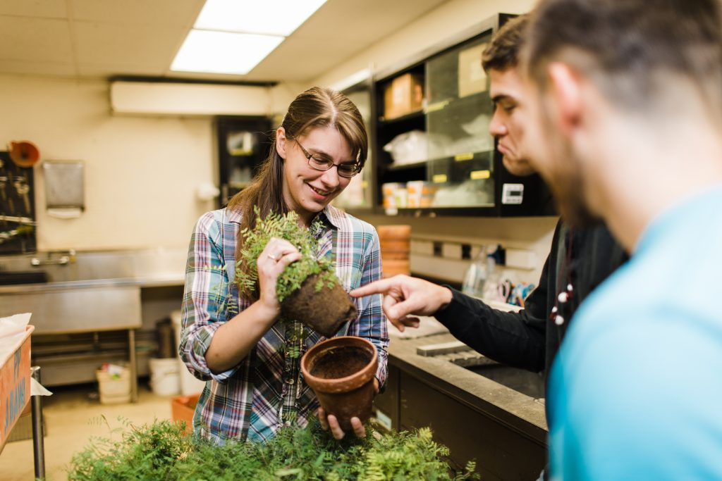 Adrienne Gorny looks at plants with students.