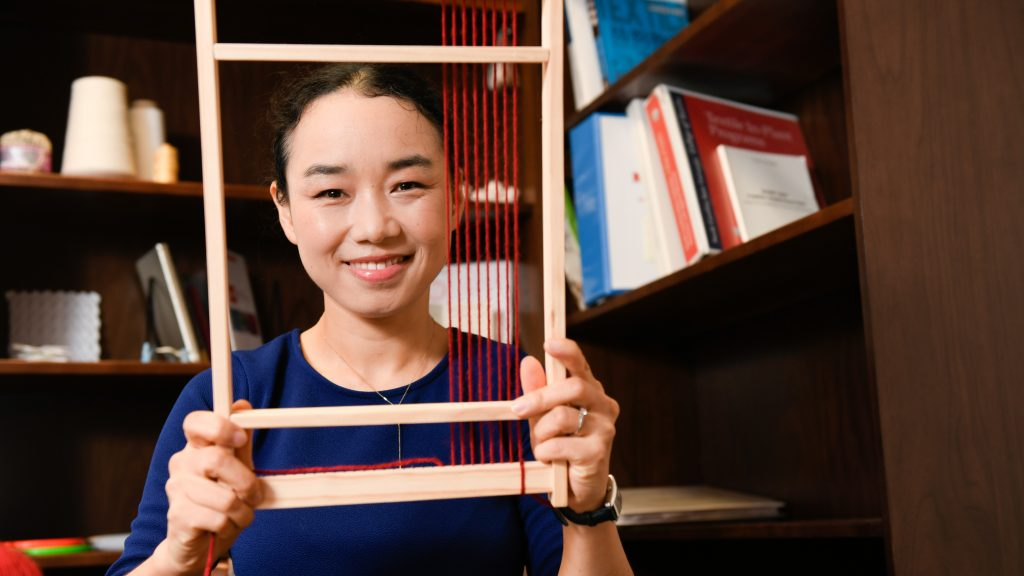 Xiaomeng Fang looks through a loom in her office.
