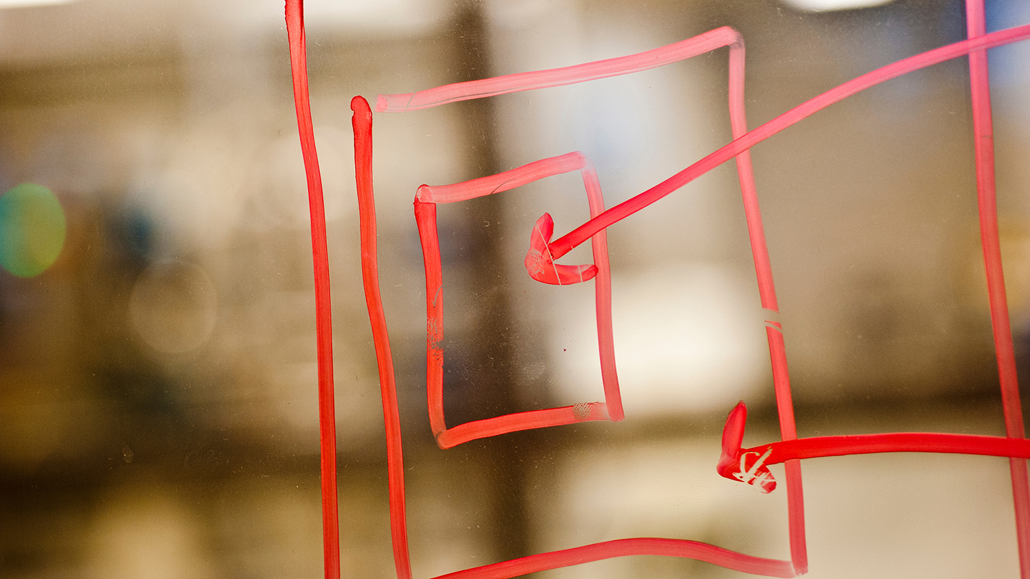 Squares and arrows drawn in red marker on a piece of backlit glass.