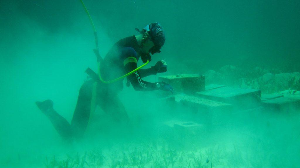 diver stacks cinderblocks on ocean floor