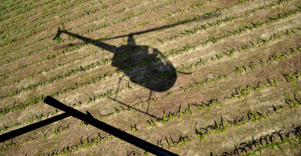 helicopter flies over field