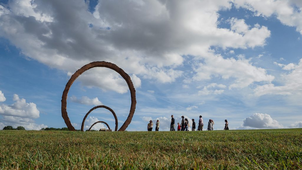 A group of students walks in front of a earthen sculpture at the NC Art Museum park.