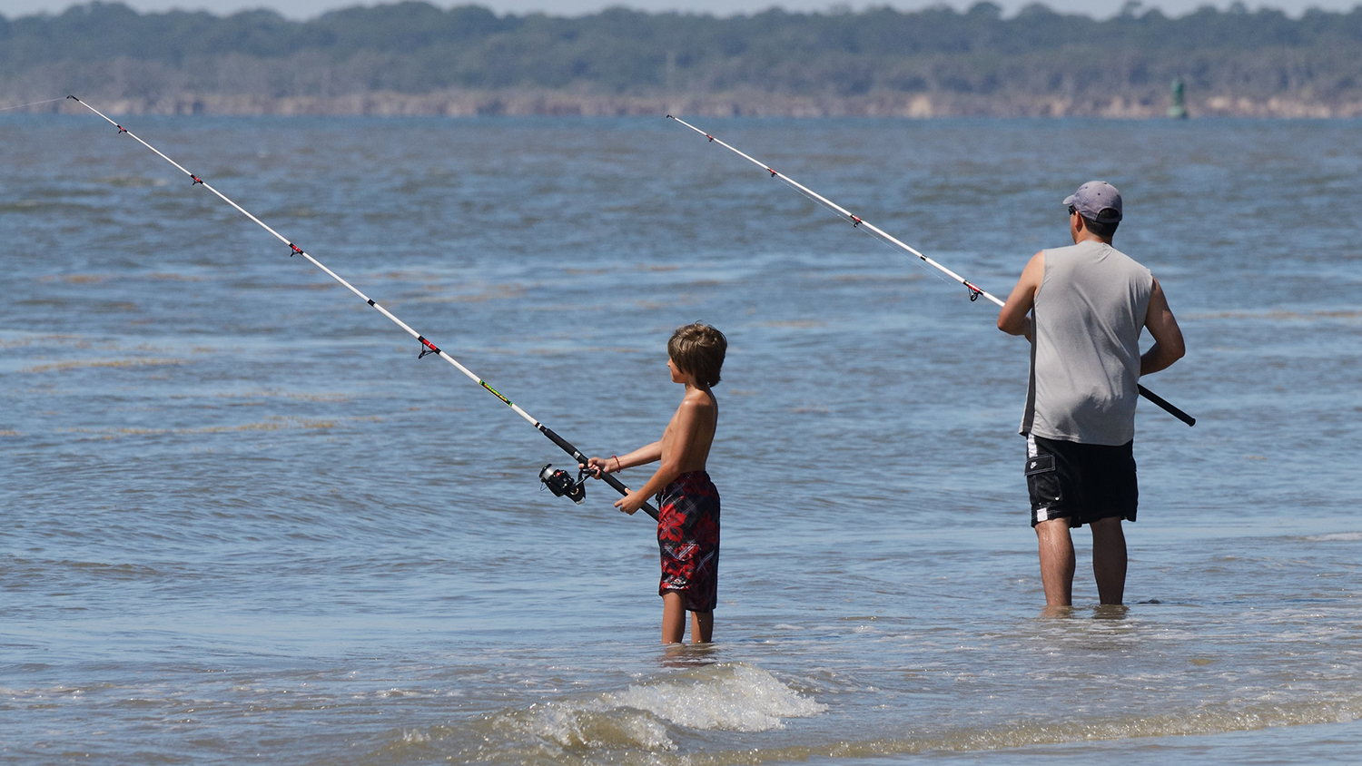 child and adult fishing on the beach