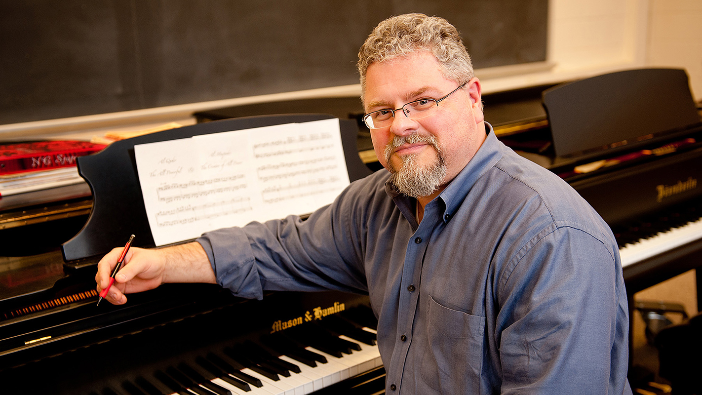 J. Mark Scearce, professor of art and design, sits at a piano.