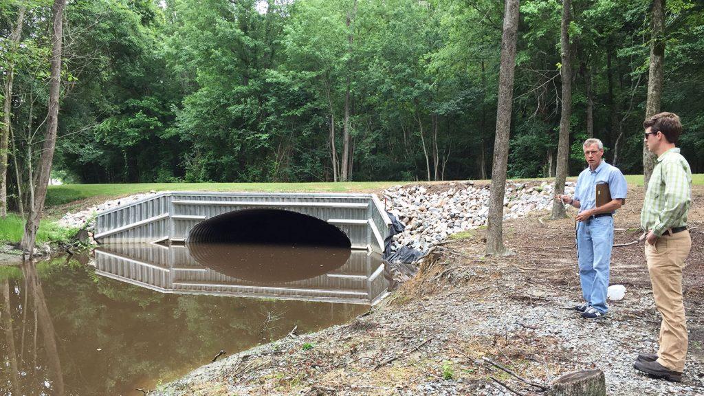 Researchers examine a bridge crossing in Bertie County that was replaced after flooding from Hurricane Matthew breached the road