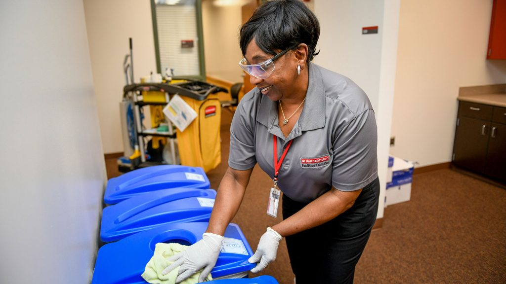 NC State housekeeping employee Benita Womack wiping a recycling bin
