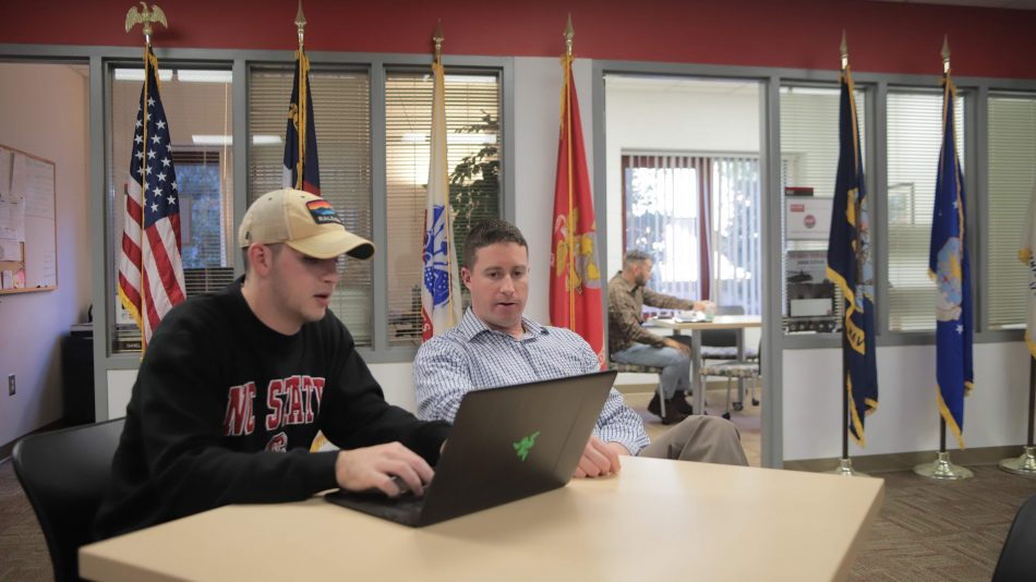 A student and a staff member talk at a table in the Military and Veteran Services Office