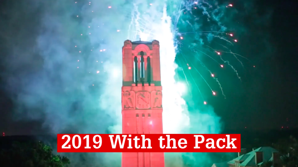 NC State's Memorial Belltower is lit red and surrounded by fireworks