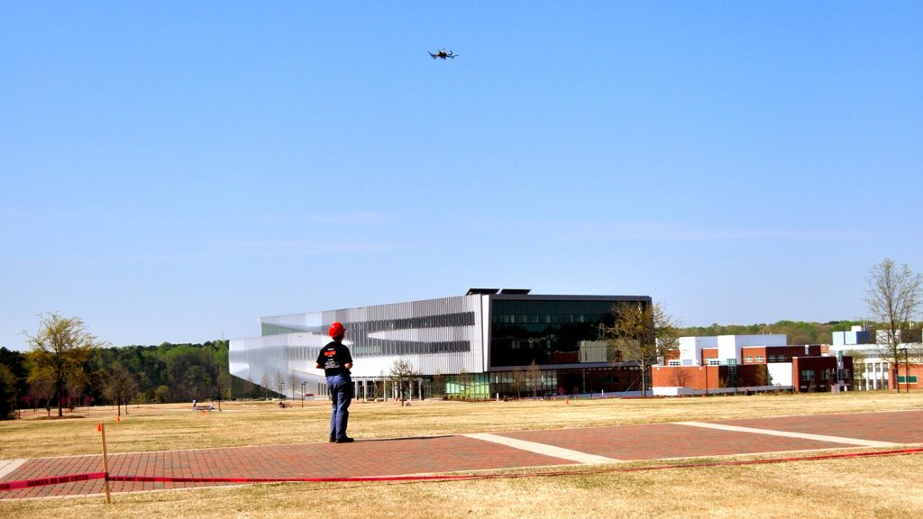 An individual flies a drone on NC State's campus