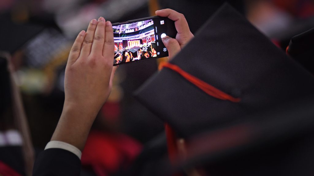 A graduate student takes a cell phone photo at the commencement ceremony