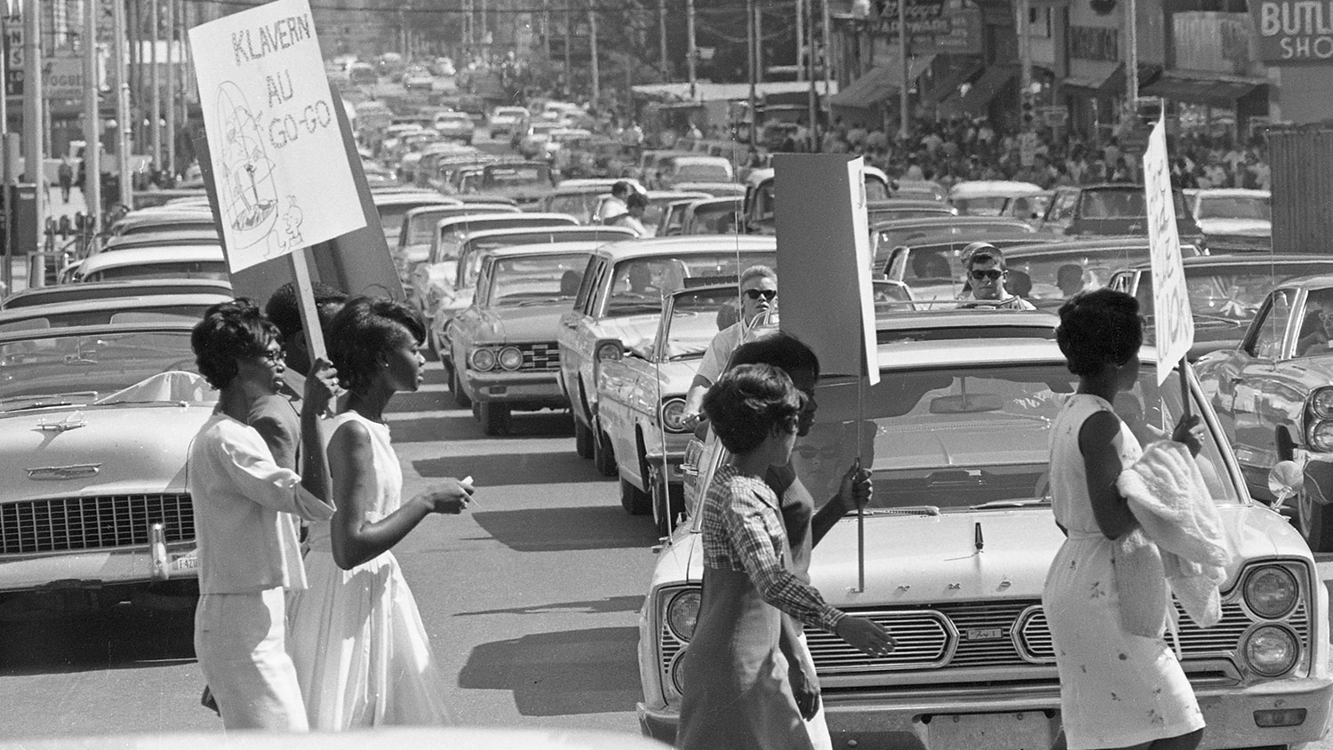 A protester crosses the street with a sign in this black and white photograph from the sixties.