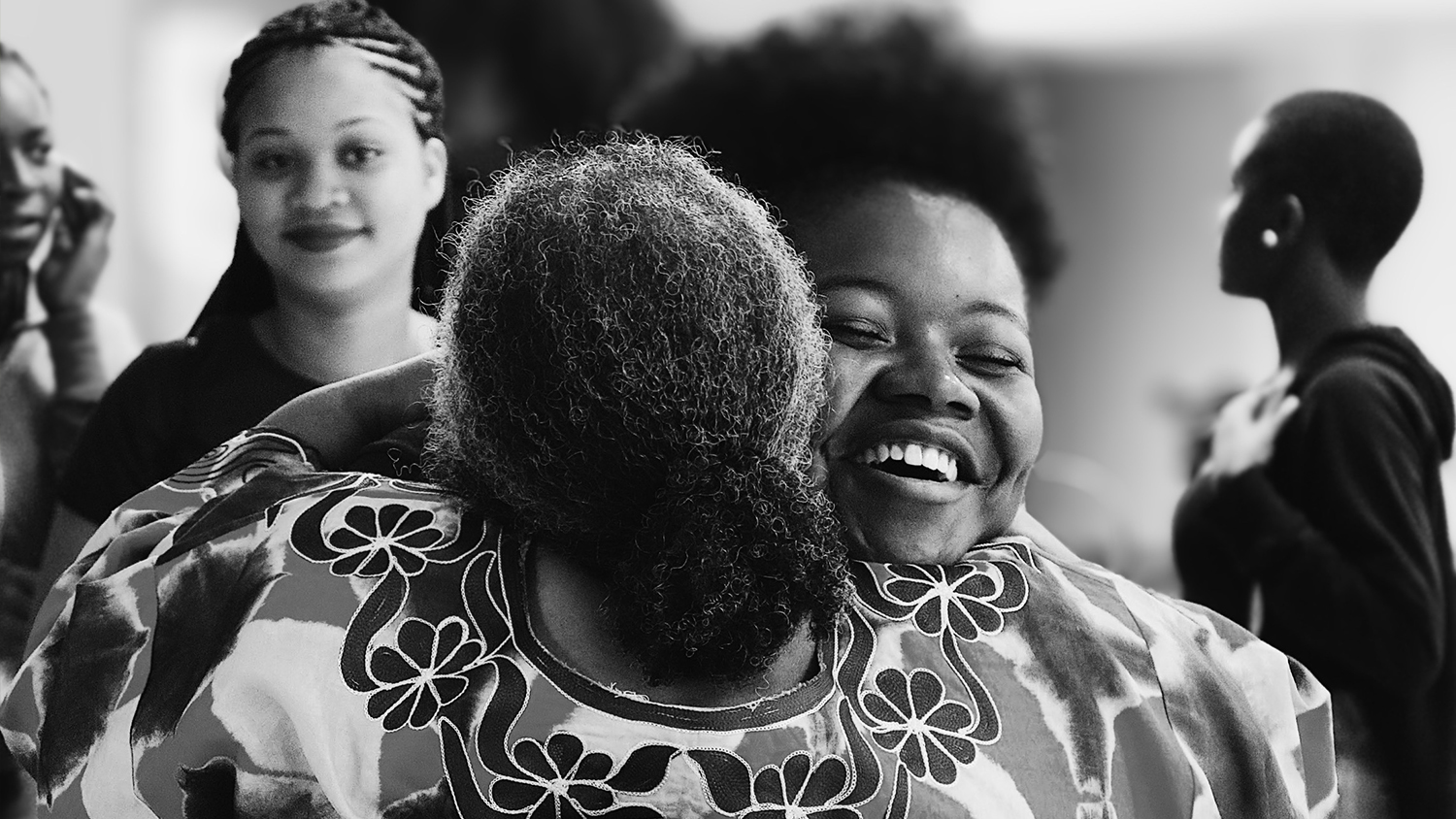 Two African-American women embrace in this black and white photo.