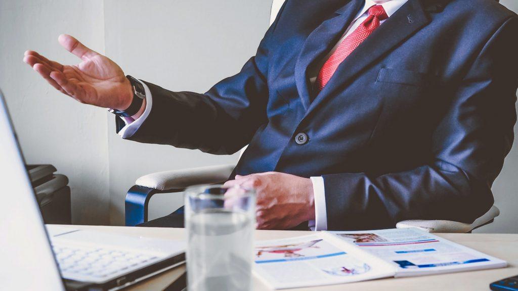man in suit behind desk