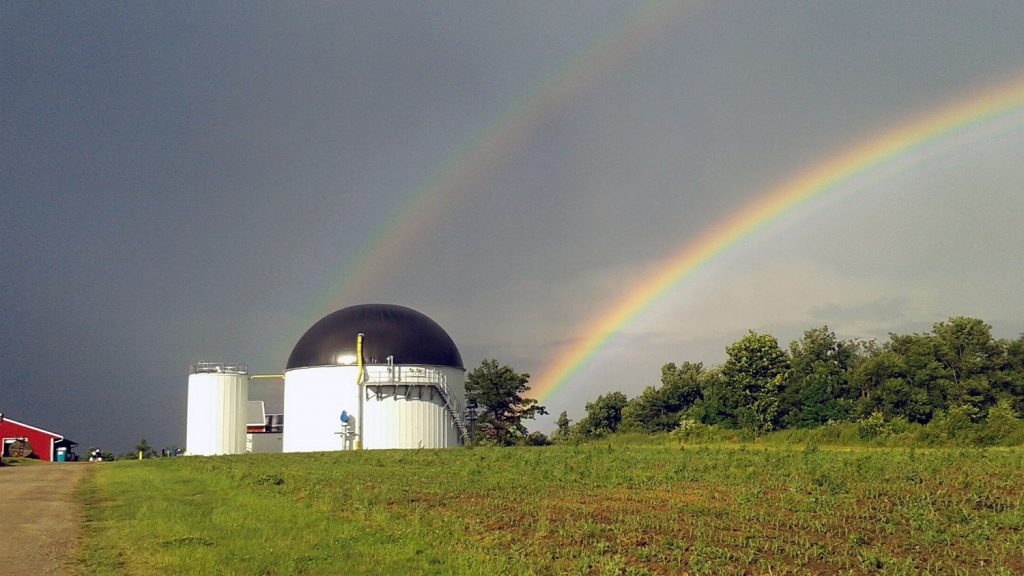 anaerobic digester on a dairy farm with rainbow in background