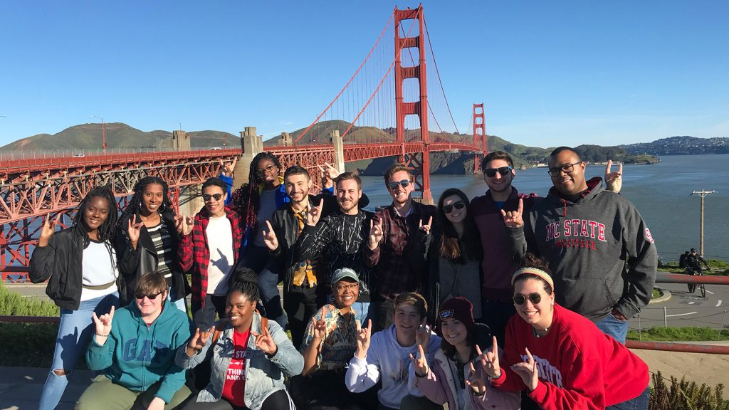 A team of students hold up wolf hands in front of the Golden Gate Bridge in San Francisco