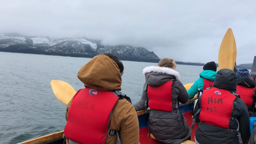 Students wearing heavy coats and lifejackets canoe across water off the coast of Alaska, with snowy mountains in the distance