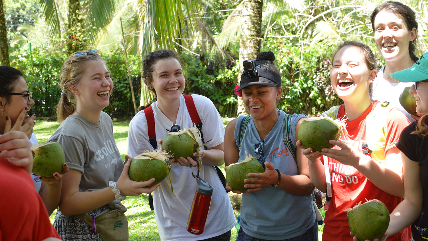 Students in Costa Rica laugh while drinking out of coconuts