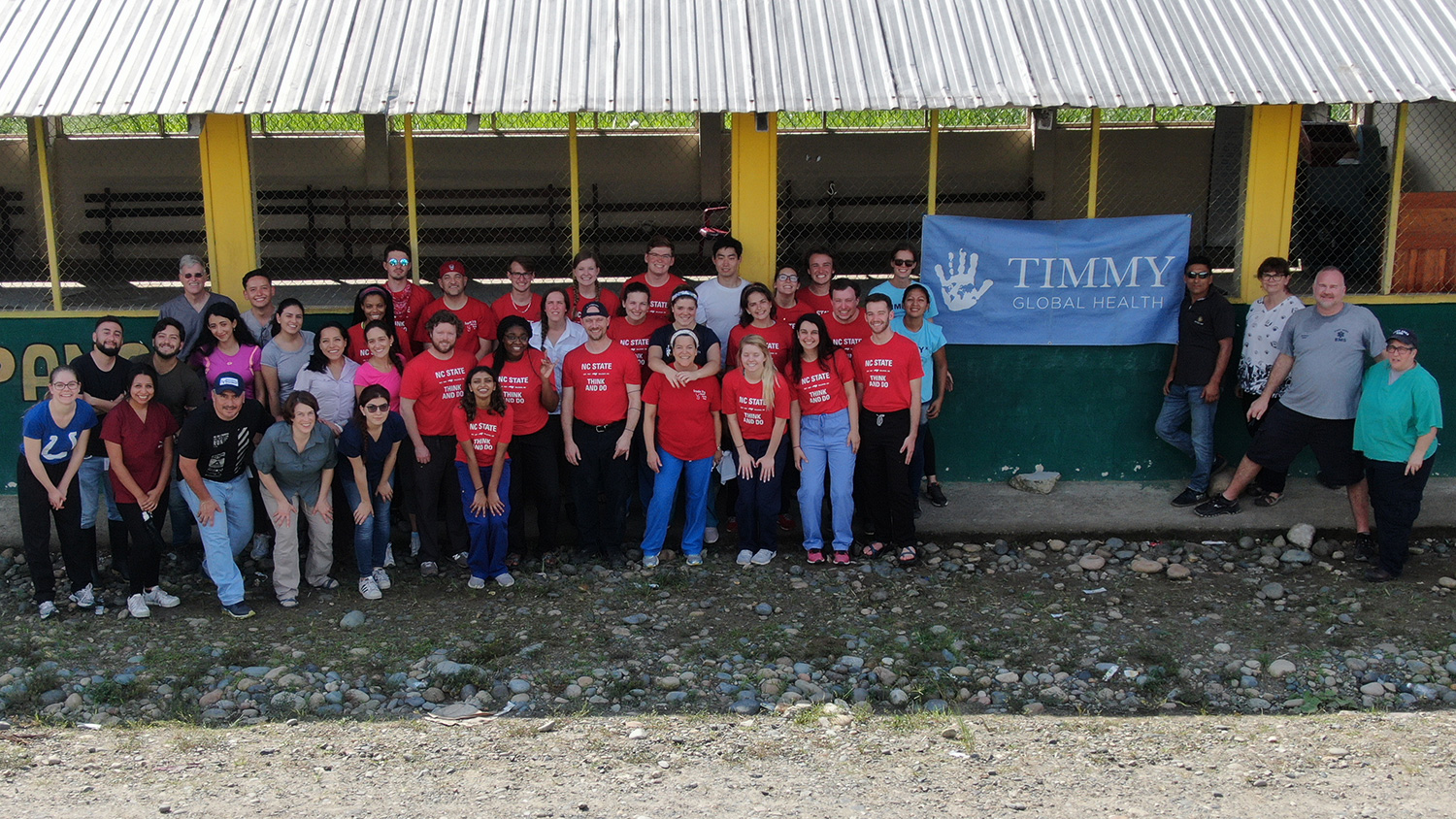 A team of students and leaders wearing NC State shirts stand outside a rural clinic in Ecuador with a TImmy Global Health banner