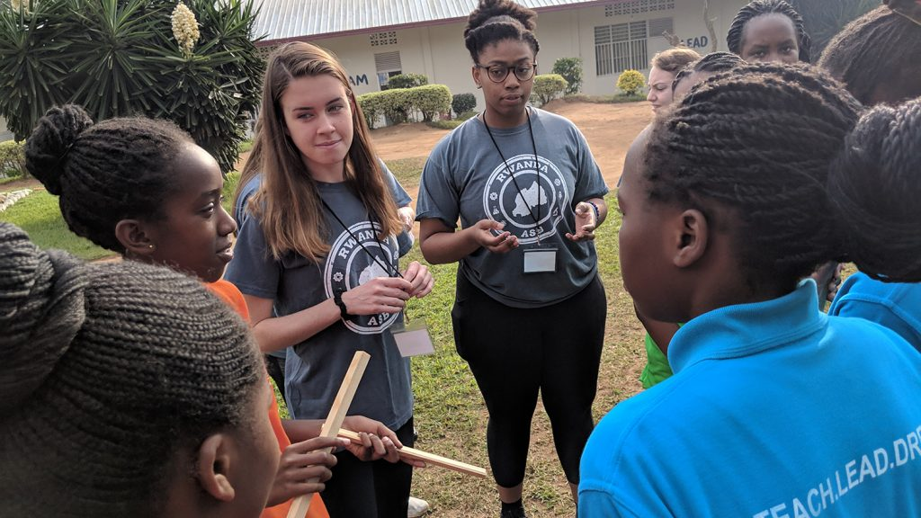 Two NC State students gather outdoors with a group of young students in Rwanda