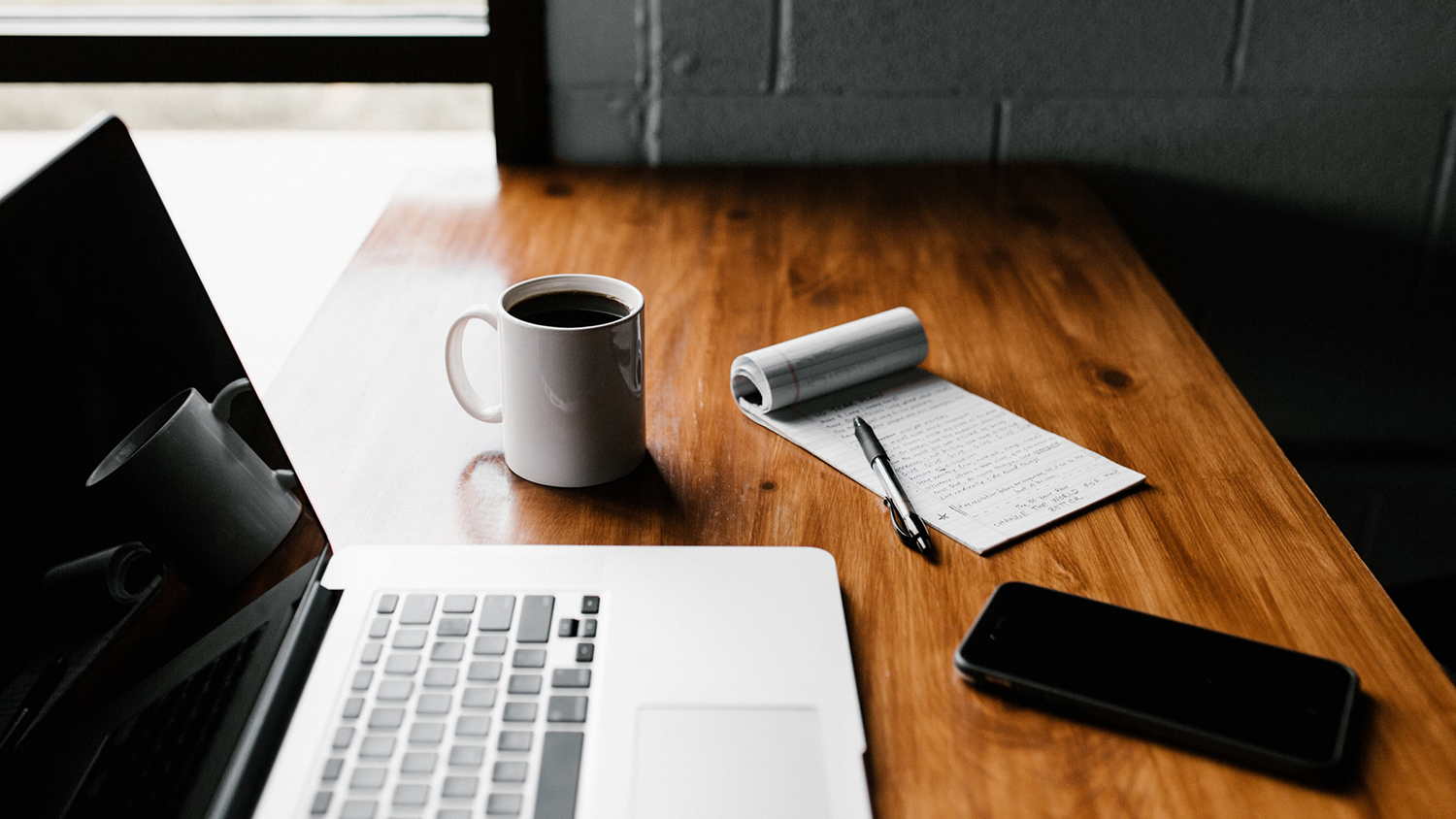 Table with laptop, smartphone and coffee cup.