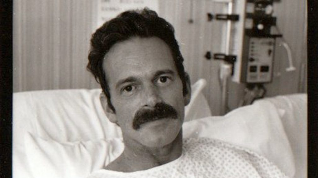 Robert Bland in a hospital bed.