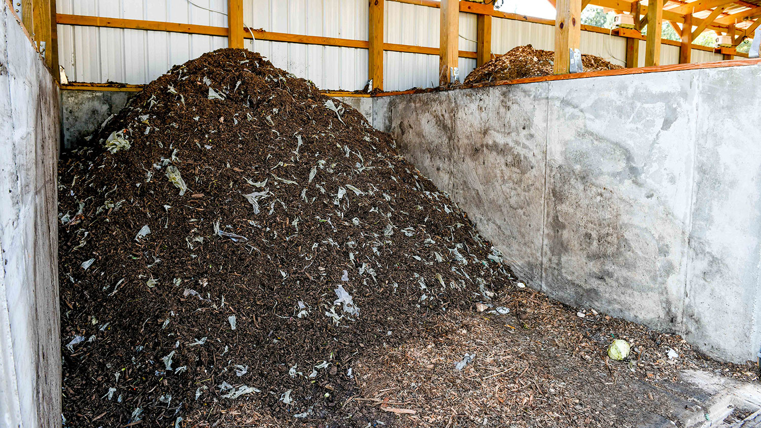 mound of organic waste in a bay at NC State's compost facility