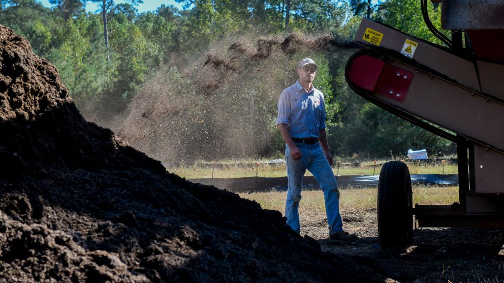 compost being added to a pile with a supervisor in the background